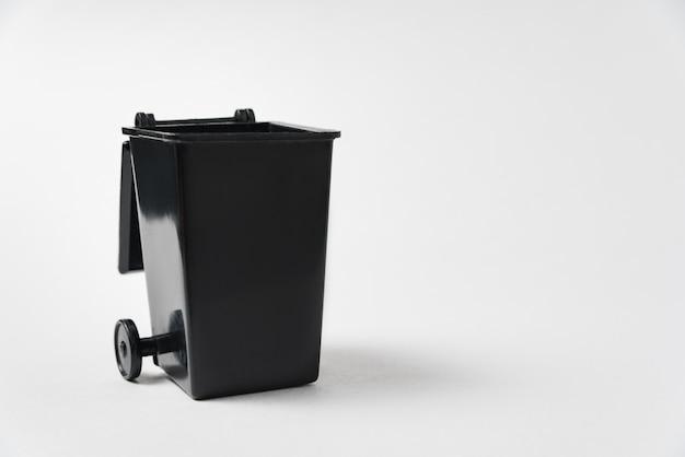 Czarny kubeł na śmieci na białym tle. śmieciarka. skopiuj miejsce