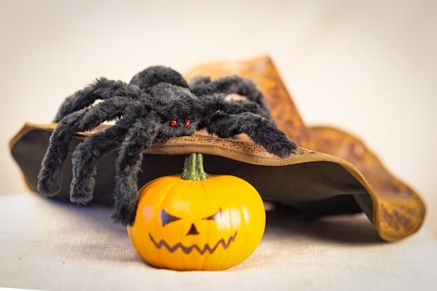 Czarny kudłaty pająk z czerwonymi oczami siedzi na kapeluszu wiedźmy, a w pobliżu leży dynia halloween.