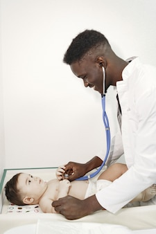 Czarny lekarz. dziecko w pieluszce. afrykanin ze stetoskopem.