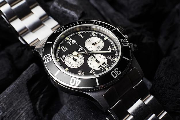 Czarny luksusowy zegarek na tle czarnych węgli