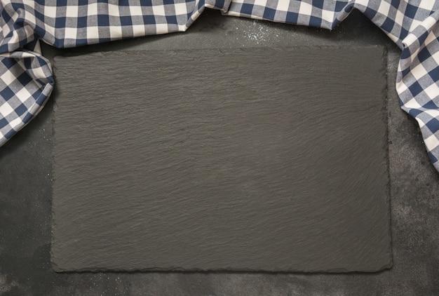 Czarny łupek z kuchennym niebieskim ręcznikiem w kratkę.