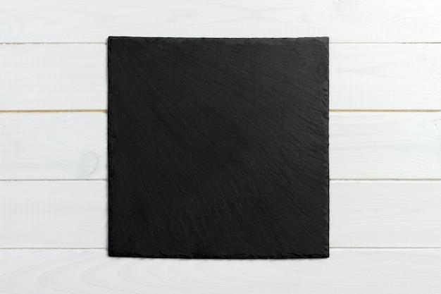 Czarny łupku kamień na drewnianym tle. kopia przestrzeń