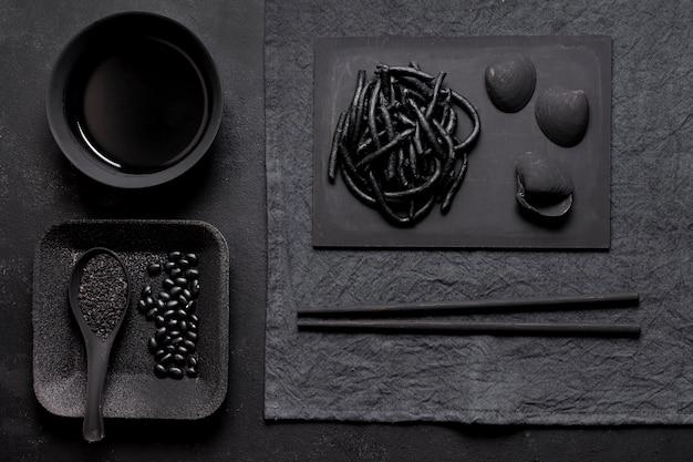 Czarny makaron krewetkowy z ciemną aranżacją małży