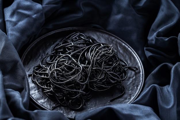 Czarny makaron na czarnym talerzu. kałamarnica atrament czarny makaron na ciemnym tle. czarne spaghetti z tuszem mątwy. skopiuj miejsce. widok z góry