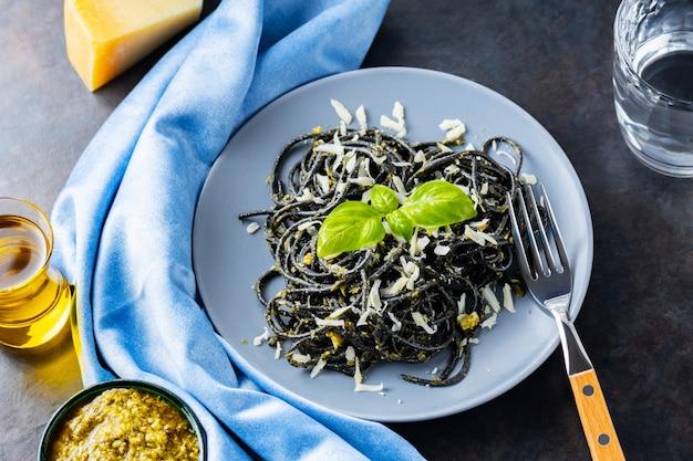 Czarny makaron z tuszem mątwy na szarym talerzu. czarne spaghetti z parmezanem