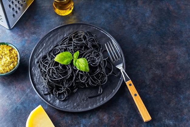 Czarny makaron z tuszem z mątwy. czarne spaghetti z sosem pesto, bazylią i parmezanem
