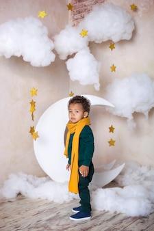 Czarny mały chłopiec w zielonym swetrze i żółtym szaliku w zamyśleniu kosztuje około miesiąca. mały książę. mały afroamerykanin. zamyślone dziecko. dziecko bawi się i bawi w przedszkolu. szkoła