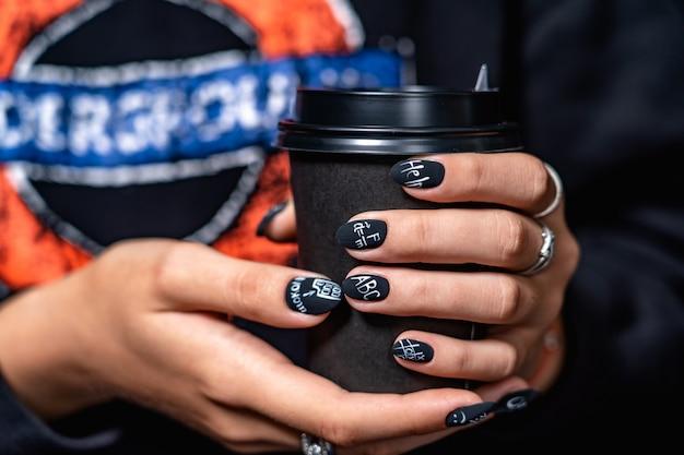 Czarny matowy manicure ma inny napis na ciemnym tle