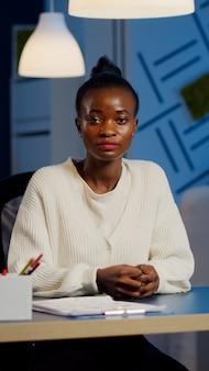 Czarny menedżer kobieta słucha partnera podczas wideokonferencji o północy z biura firmy planowania strategii finansowej. pani korzystająca z nowoczesnej technologii sieci bezprzewodowej dyskutuje na wirtualnym spotkaniu