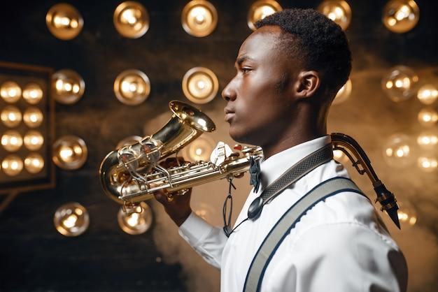 Czarny męski wykonawca jazzowy pozuje z saksofonem na scenie z reflektorami. czarny jazzman występuje na scenie