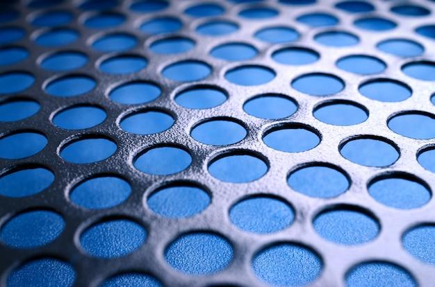 Czarny metalowy panel obudowy komputera z otworami na niebieskim tle. streszczenie bliska obraz