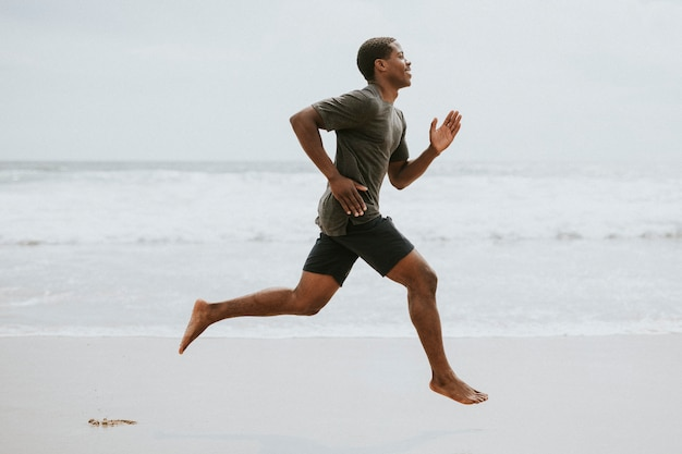 Czarny mężczyzna biegający po plaży