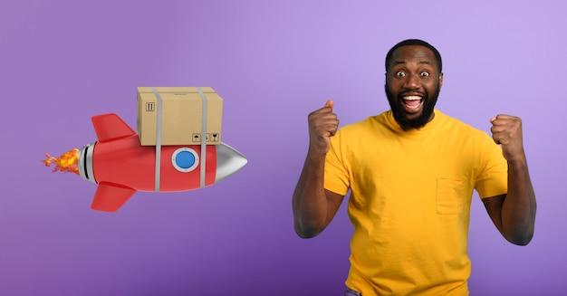 Czarny mężczyzna cieszy się z otrzymania paczki. koncepcja szybkiej dostawy jak rakieta. fioletowe tło