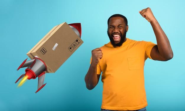 Czarny mężczyzna cieszy się z otrzymania paczki. koncepcja szybkiej dostawy jak rakieta.