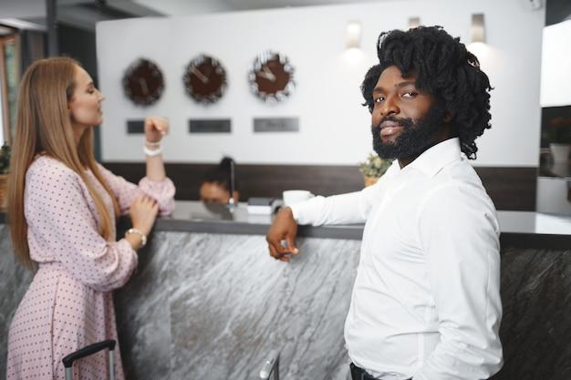 Czarny mężczyzna i kaukaski kobieta koledzy przedsiębiorców meldowania się w recepcji hotelu