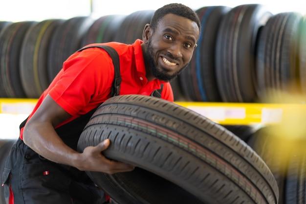 Czarny mężczyzna mechanik trzyma oponę i pokazuje opony w serwisie samochodowym i sklepie samochodowym. mechanik fachowy pracujący w warsztacie samochodowym.