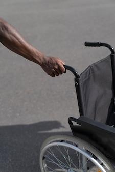 Czarny mężczyzna ręka trzyma na białym tle wózek inwalidzki na drodze