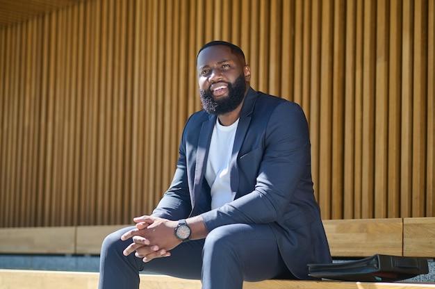Czarny mężczyzna siedzący na ławce i czekający na kogoś