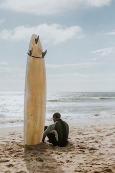 Czarny mężczyzna siedzący przy swojej desce surfingowej