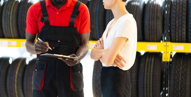 Czarny mężczyzna sprzedawca pokazuje opony do klienta kaukaski kobieta w serwisie samochodowym i sklepie samochodowym.