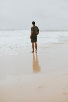 Czarny mężczyzna stojący nad morzem