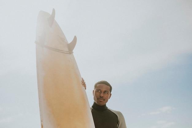 Czarny mężczyzna stojący przy desce surfingowej