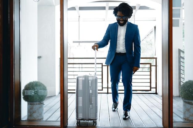 Czarny mężczyzna wchodzi do drzwi hotelu z zapakowaną walizką