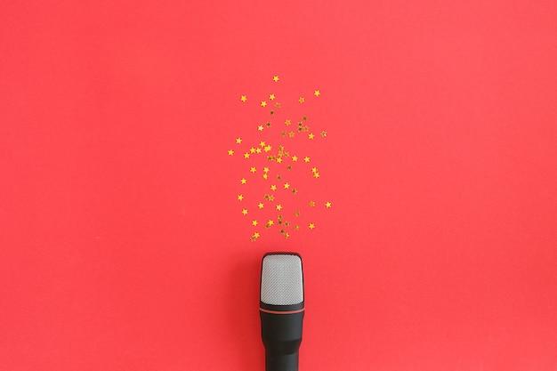 Czarny mikrofon i złote gwiazdy konfetti na czerwonym tle. impreza muzyczna lub karaoke.
