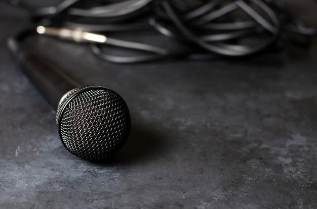 Czarny mikrofon na ciemnym betonowym stole. sprzęt do śpiewu, wywiadów lub reportaży. skopiuj miejsce