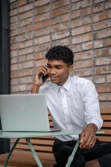 Czarny młody człowiek rozmawia przez telefon na tle brązowego muru. facet w białej koszuli korzysta ze smartfona i laptopa. praca zdalna poza biurem. zdjęcie pionowe.