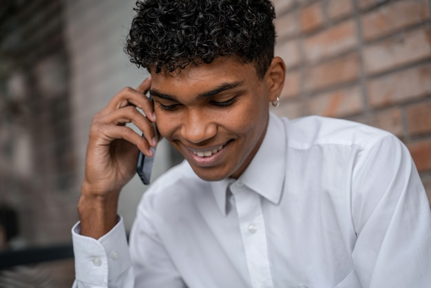 Czarny młody człowiek rozmawia przez telefon na tle brązowego muru. facet w białej koszuli używa smartfona