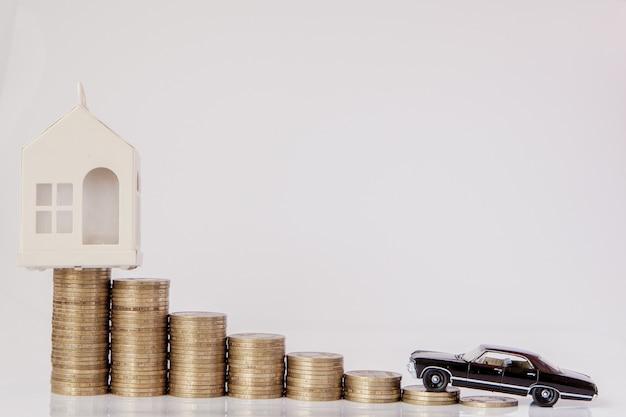 Czarny model samochodu i domu z monetami w postaci histogramu na białym tle. pojęcie pożyczek, oszczędności, ubezpieczeń.