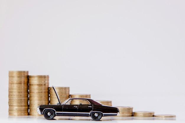 Czarny model samochodu z monetami w postaci histogramu na białym tle. pojęcie pożyczek, oszczędności, ubezpieczeń.