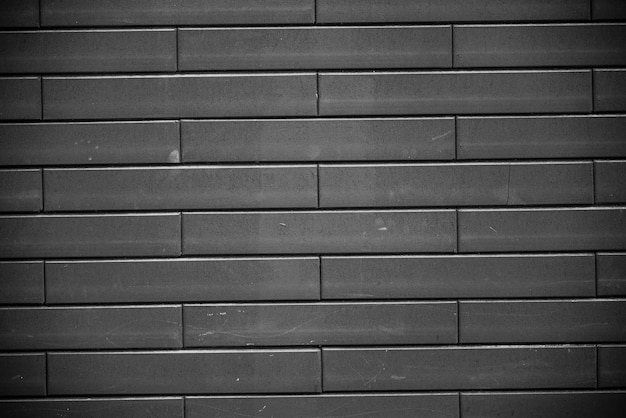 Czarny mur z cegły. miejski czarny ceglany mur tekstura tło murowane.