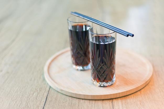 Czarny napój ze słomkami dwie szklanki koktajlu herbacianego cuba libre z rumem cola z limonką lodową ze słomkami