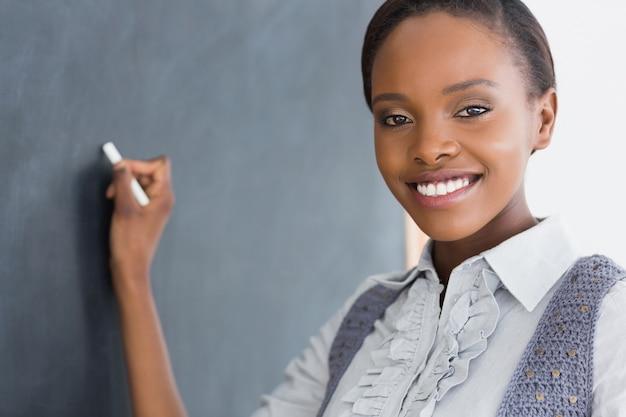 Czarny nauczyciel trzyma kredę podczas gdy ono uśmiecha się