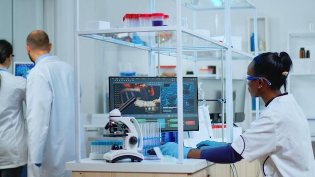 Czarny naukowiec prowadzący badania nad nową szczepionką w nowocześnie wyposażonym laboratorium. wieloetniczny zespół badający ewolucję wirusa przy użyciu zaawansowanych technologii do badań naukowych nad opracowaniem leczenia przeciw covid19.