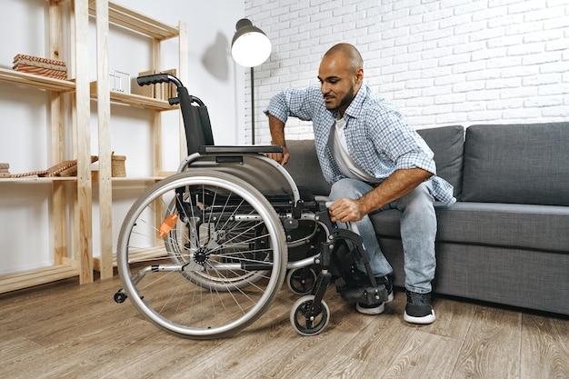 Czarny niepełnosprawny mężczyzna siada w domu na wózku inwalidzkim