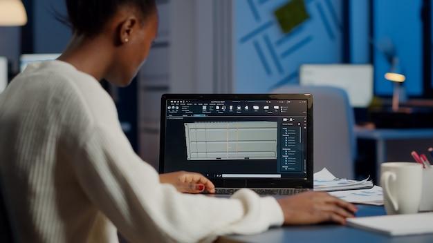 Czarny niezależny architekt pracujący w oprogramowaniu 3d do opracowania projektu kontenera siedzący przy biurku w biurze firmy o północy. skoncentrowany inżynier tworzący i badający prototyp, analizujący model w skali