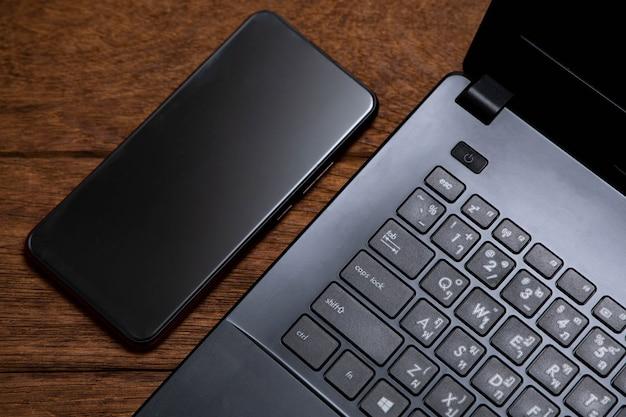 Czarny notatnik i czarny telefon komórkowy na drewnianym stole