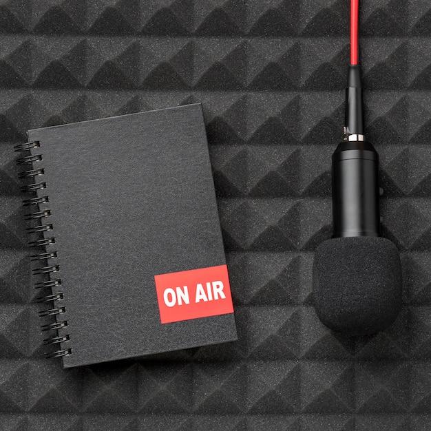 Czarny notatnik i mikrofon z czerwonym przewodem