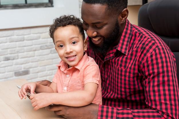 Czarny ojciec i śliczny syn używa pastylkę