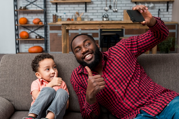 Czarny ojciec i syn bierze selfie pokazuje aprobaty