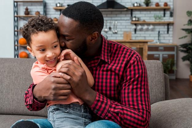 Czarny ojciec przytulanie syna na kanapie