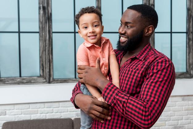 Czarny ojciec trzyma syna w ramiona