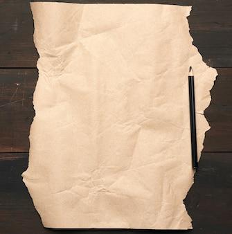 Czarny ołówek i nieskręcony brązowy papier na drewnianej powierzchni ze starych desek