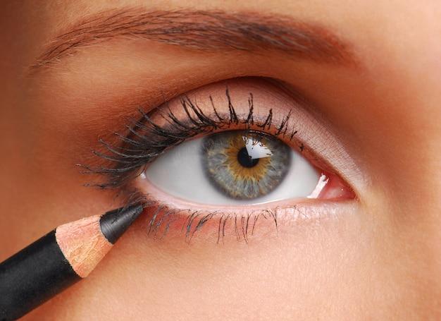 Czarny ołówek kosmetyczny. piękne kobiety oko z bliska.