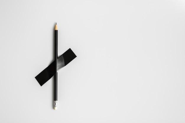 Czarny ołówek przypięty czarną taśmą z tkaniny.