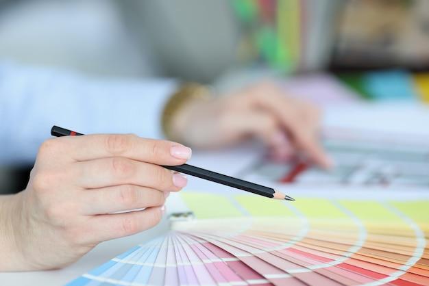 Czarny ołówek w dłoni nad paletą kolorów