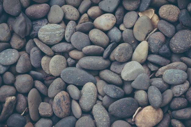 Czarny otoczaka kamienia tło z rocznika filtrem